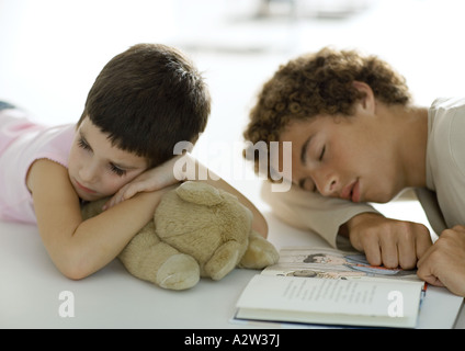 Adolescent boy and younger sibling falling asleep while reading book - Stock Photo