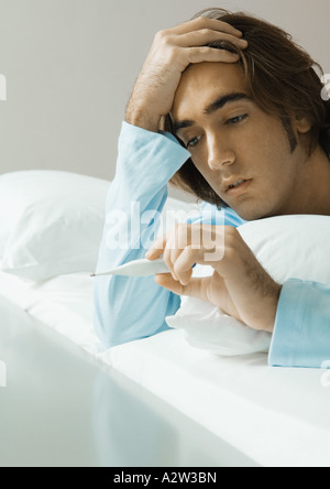 Man lying in bed, looking at thermometer - Stock Photo