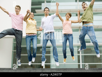 Teens holding hands and jumping in the air - Stock Photo