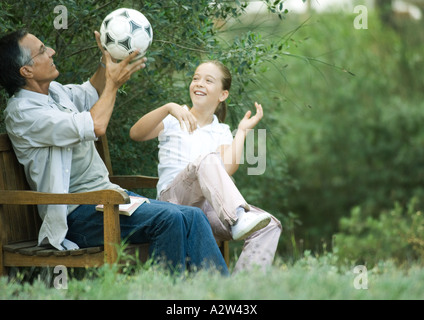 Girl and grandfather sitting together, playing with soccer ball - Stock Photo