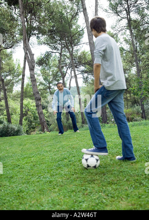 Mature man and teenage boy playing soccer - Stock Photo