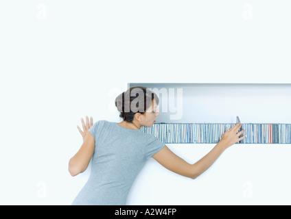 Woman taking CD from shelf - Stock Photo
