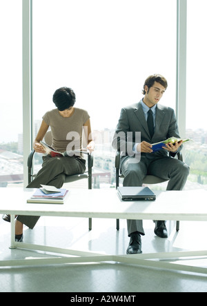 Professional man and woman sitting in lobby, looking at magazines - Stock Photo