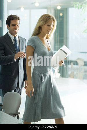 Professional man and woman stepping away from table - Stock Photo