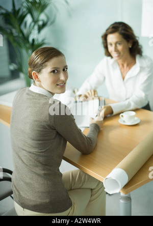 Woman sitting at table across from architect, smiling over shoulder at camera - Stock Photo