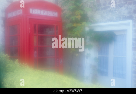 Atmospheric old style UK red telephone box squeezed in a corner between a hedge and stone brick house - Stock Photo
