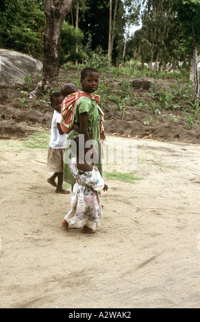 Young girl carrying a baby on her back in Nkhotakota, Lake Malawi, Malawi - Stock Photo
