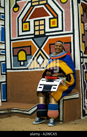 Ndebele woman dressed in traditional costume Married woman Traditional geometric wall paintings in background South - Stock Photo