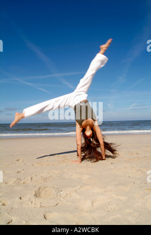 Lifestyle young woman 20+ doing gymnastics and jumping on beach happy holidays beach sand ocean vitality - Stock Photo