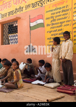 Rows of well behaved junior school children sat on ground in shade outside rural village school for outdoor lesson - Stock Photo