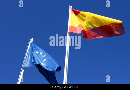spanish and eu flags on flagpoles flying against a blue sky North Tenerife Canary Islands Spain - Stock Photo