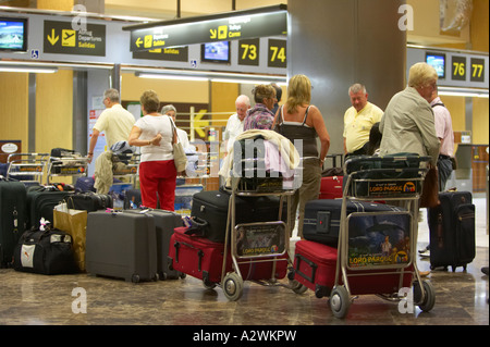 passengers queue with baggage at check in desk at Reina Sofia Sur TFS South Airport Tenerife Canary Islands Spain - Stock Photo