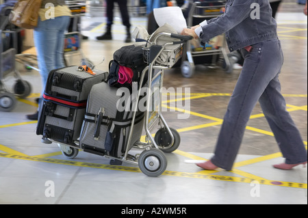 female passenger pushes luggage on trolley out of Reina Sofia Sur TFS South Airport Tenerife Canary Islands Spain - Stock Photo