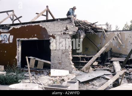 Vukovar, Croatia, under Serb control,  Feb 1992: a man laughs as he salvage what he can from the wreckage of his - Stock Photo