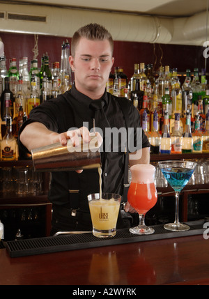 Barman pours a Whiskey Sour The Cocktails from the left Whiskey Sour Planters Punch Blue Lady - Stock Photo