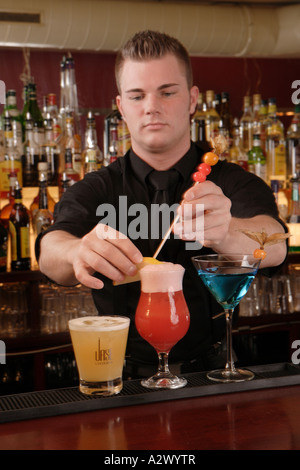 Barman prepares a Planters Punch The Cocktails from the left Whiskey Sour Planters Punch Blue Lady - Stock Photo