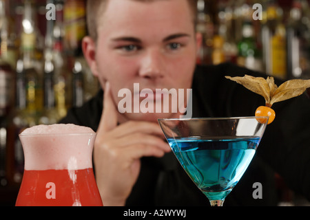Barman checks cocktails The Cocktails from the left Planters Punch Blue Lady - Stock Photo