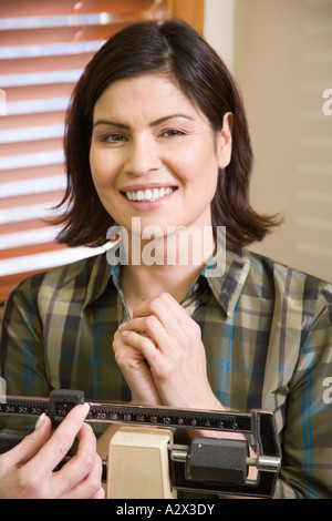 Female patient is weighted by a nurse in a medical office. - Stock Photo