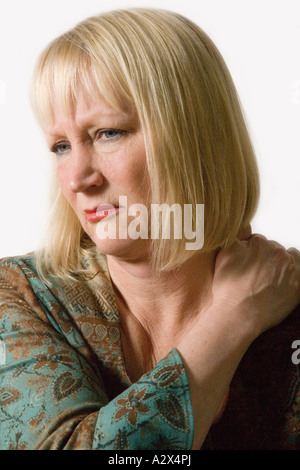 Middle aged woman experiencing shoulder pain. - Stock Photo