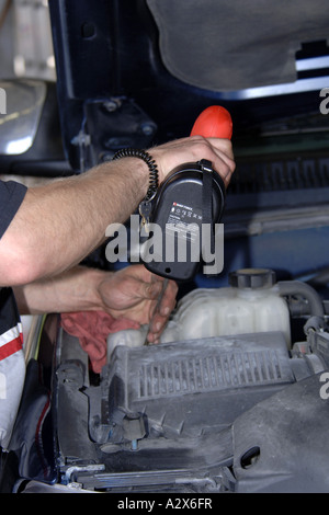 Vehicle Technician using a chordless drill on a vehicle filter cap during an oil service. - Stock Photo