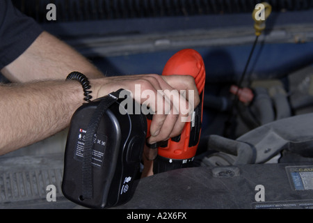 Vehicle Technician using a chord-less drill on a vehicle filter cap during an oil service. - Stock Photo