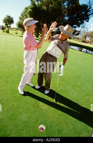 Retirement age man and woman enjoying game of golf together. - Stock Photo