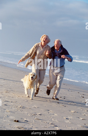 Retired couple running on the beach with their pet Labrador dog.