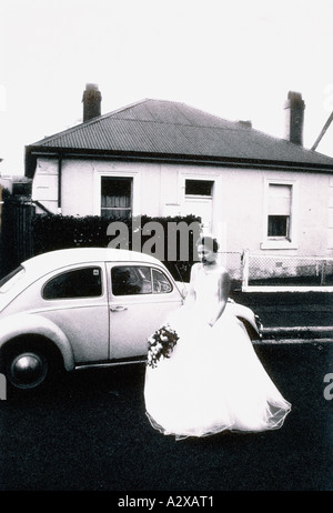 Young woman in wedding dress standing by classic Volkswagen Beetle car outside house. - Stock Photo