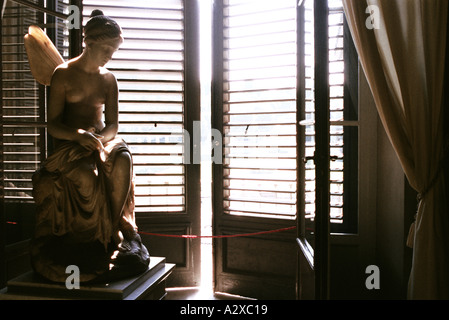 Carved stone statue of angel in front of slightly open wooden window shutters in window in Florence, Italy - Stock Photo