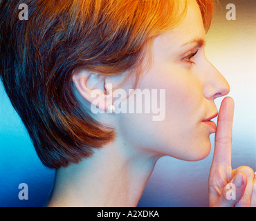 Indoor studio portrait side view profile of young woman with finger held to mouth. - Stock Photo
