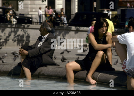 People dipping their feet in the fountains at 'Trafalgar Square' - Stock Photo