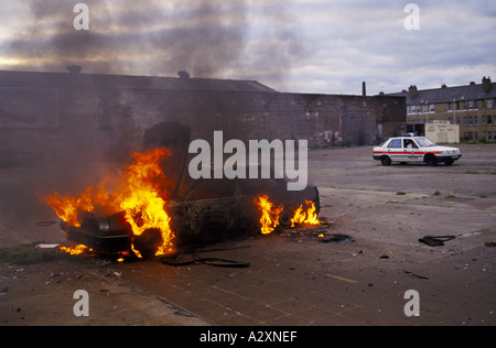 GLASGOW, SCOTLAND, A CAR STOLEN BY JOY-RIDERS BURNS IN POSSIL PARK, A RUN DOWN ESTATE, A POLICE CAR DRIVES BY, - Stock Photo