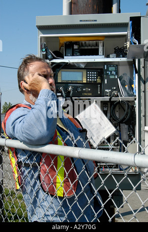 Adult male telephone technician works on a communications problem outside - Stock Photo