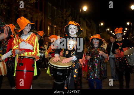 children dressed up and carrying drums parade down shipquay street Halloween Derry Ireland - Stock Photo