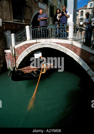 gondola passing under a street bridge in venice italy - Stock Photo
