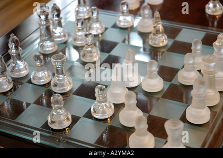 Glass pieces on a wooden chess board - Stock Photo