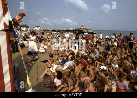 children on the beach watching punch judy puppet show at broadstairs kent - Stock Photo