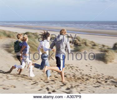 Group of friends running on beach - Stock Photo