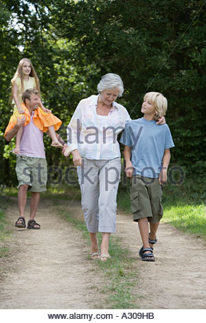 Family walking on a dirt track - Stock Photo