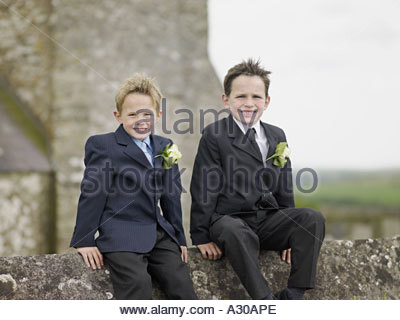 Two boys on wall outside church - Stock Photo