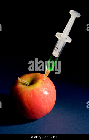 Apple injected with green liquid Concept to represent genetically modified food - Stock Photo
