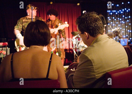 Professional couple watching Artie Fishel (aka Gilad Atzmon) and The Promised Band over dinner - Stock Photo