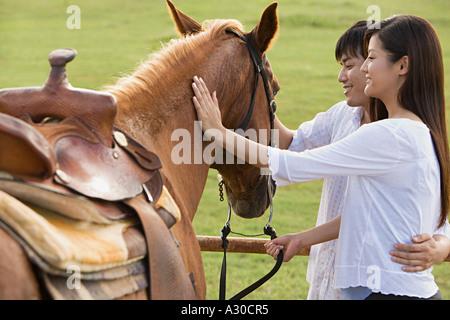 Couple stroking horse - Stock Photo