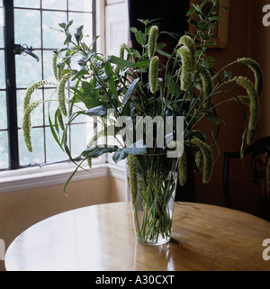 Glass vase with wild grasses on circular wooden table - Stock Photo