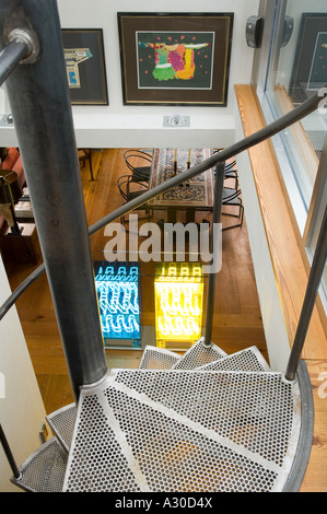 View from top of spiral staircase looking down into open plan living area with neon light installation in penthouse - Stock Photo