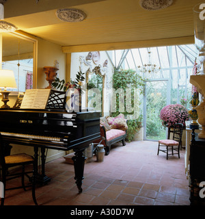 Grand piano in flagstone floored conservatory - Stock Photo