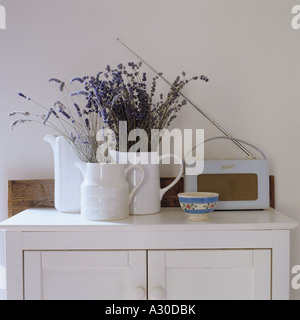 White porcelain jugs filled with lavender on top of a wooden cupboard - Stock Photo