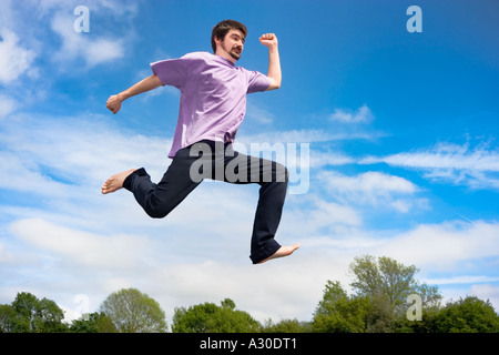Young man jumping in air, low angle view, - Stock Photo