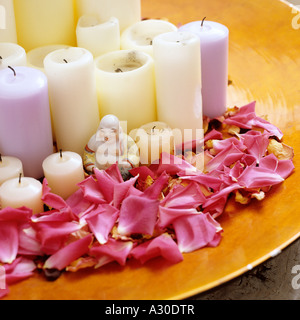 Buddha statue with candles and flower petals - Stock Photo