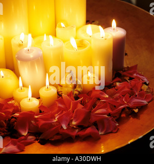 Lit candles in a bowl with rose petals and a Buddha statue - Stock Photo